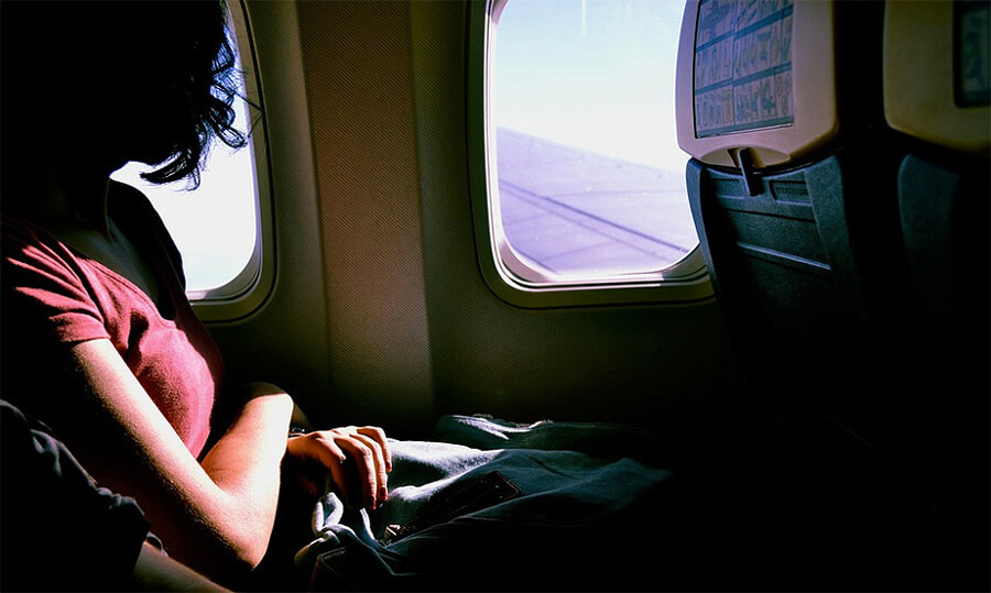girl looks outside airplane window